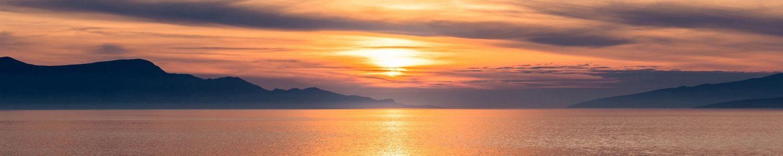 Sonnenuntergang über Meer mit Küste